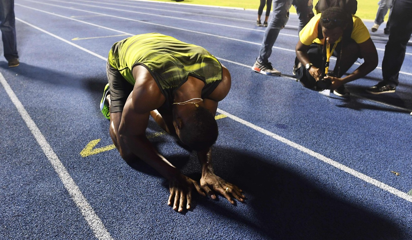 Usain Bolt Kneels To Kiss The Track At The National Stadium In Kingston,  Jamaica Photo: Afp