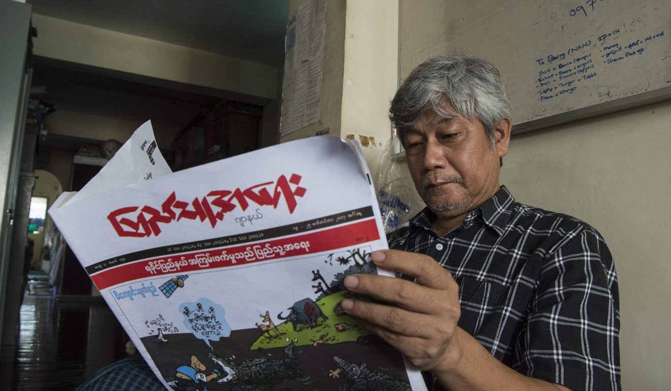 "Win Naing, one of Myanmar's most famous cartoonists, reads a newspaper carrying one of his sketches, called ""Crocodile Tears"", on the front page. Cartoons taking aim at Rohingya Muslims are spreading rapidly across social media in mainly Buddhist Myanmar. Picture: AFP"