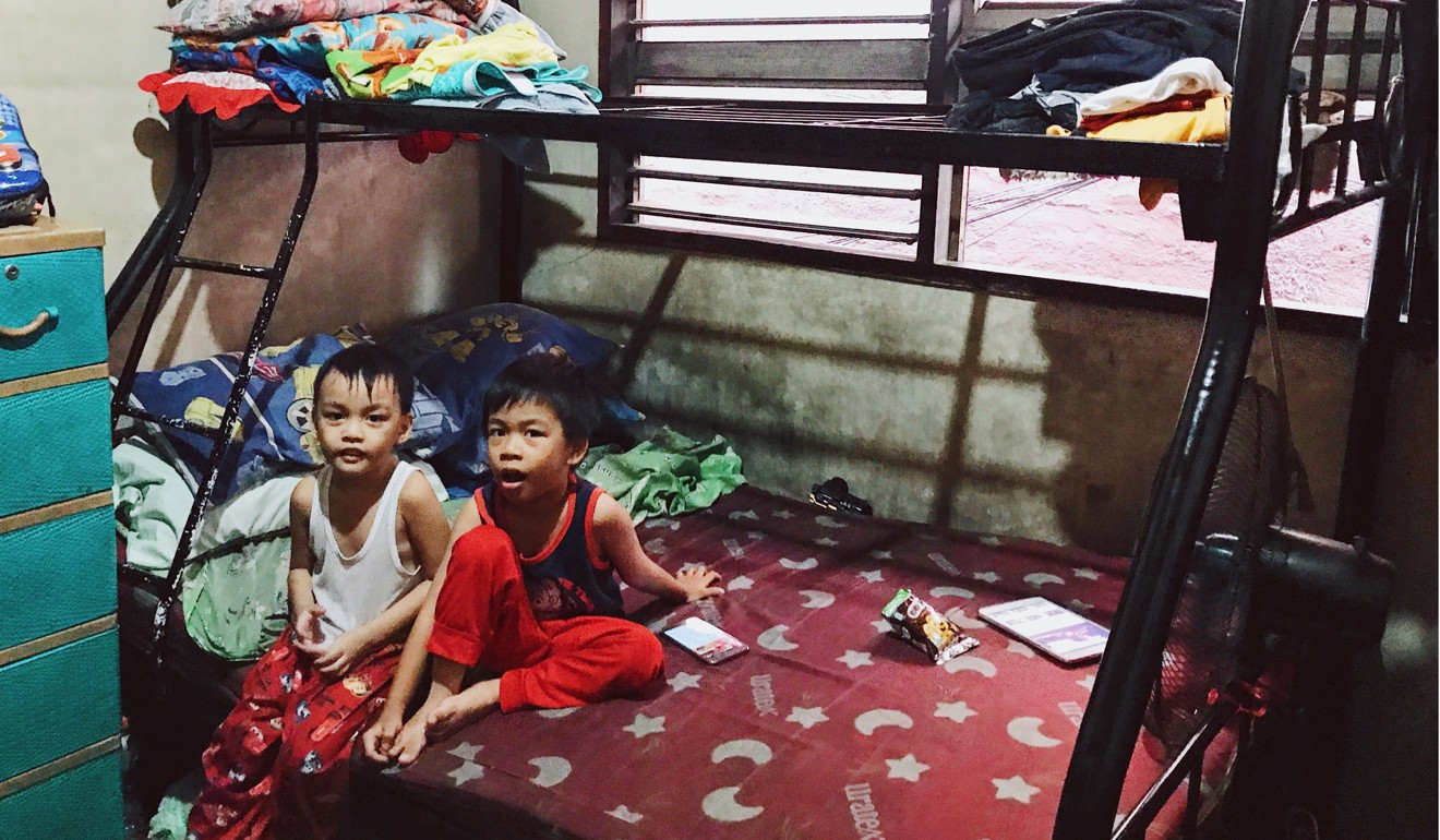 Two of Manuel S. Adad's three sons sit in their family home, which is made up of just two bedrooms, with four bunk beds and some mattresses on the floor.