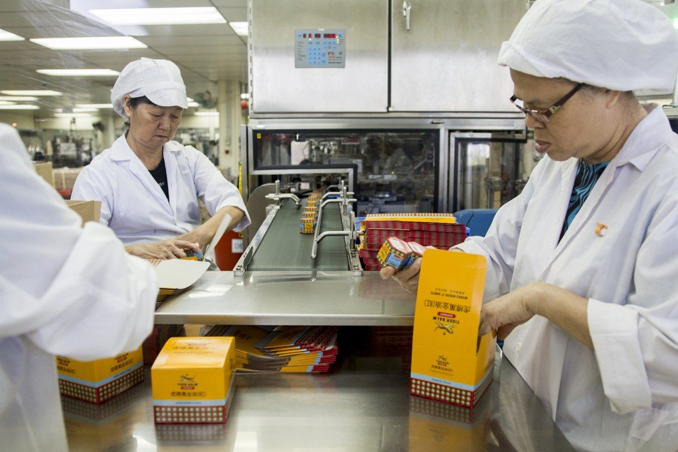 Workers pack Tiger Balm at the Haw Par Corporation's Tiger Balm factory in Singapore. Photo: Christopher DeWolf