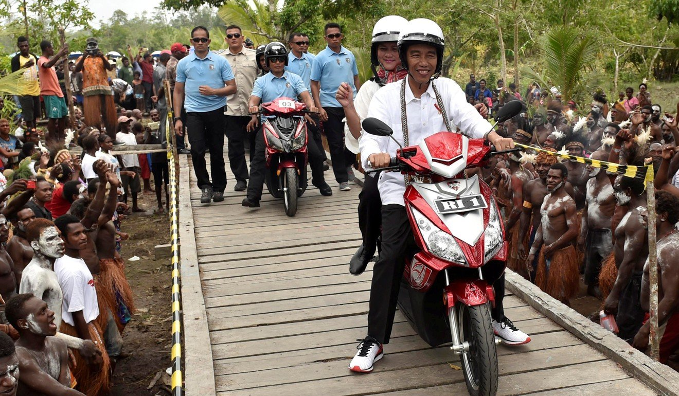 Indonesia President Joko Widodo, with his wife Iriana, drives an electric motorbike during a visit to Agats district in Asmat, Papua province, Indonesia. Photo: Reuters