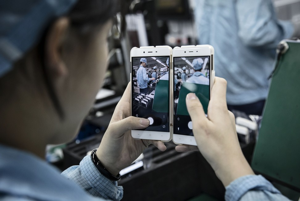 An employee tests the cameras of OnePlus smartphones at the company's manufacturing facility in the southern coastal city of Dongguan, in Guangdong province. Photo: Bloomberg