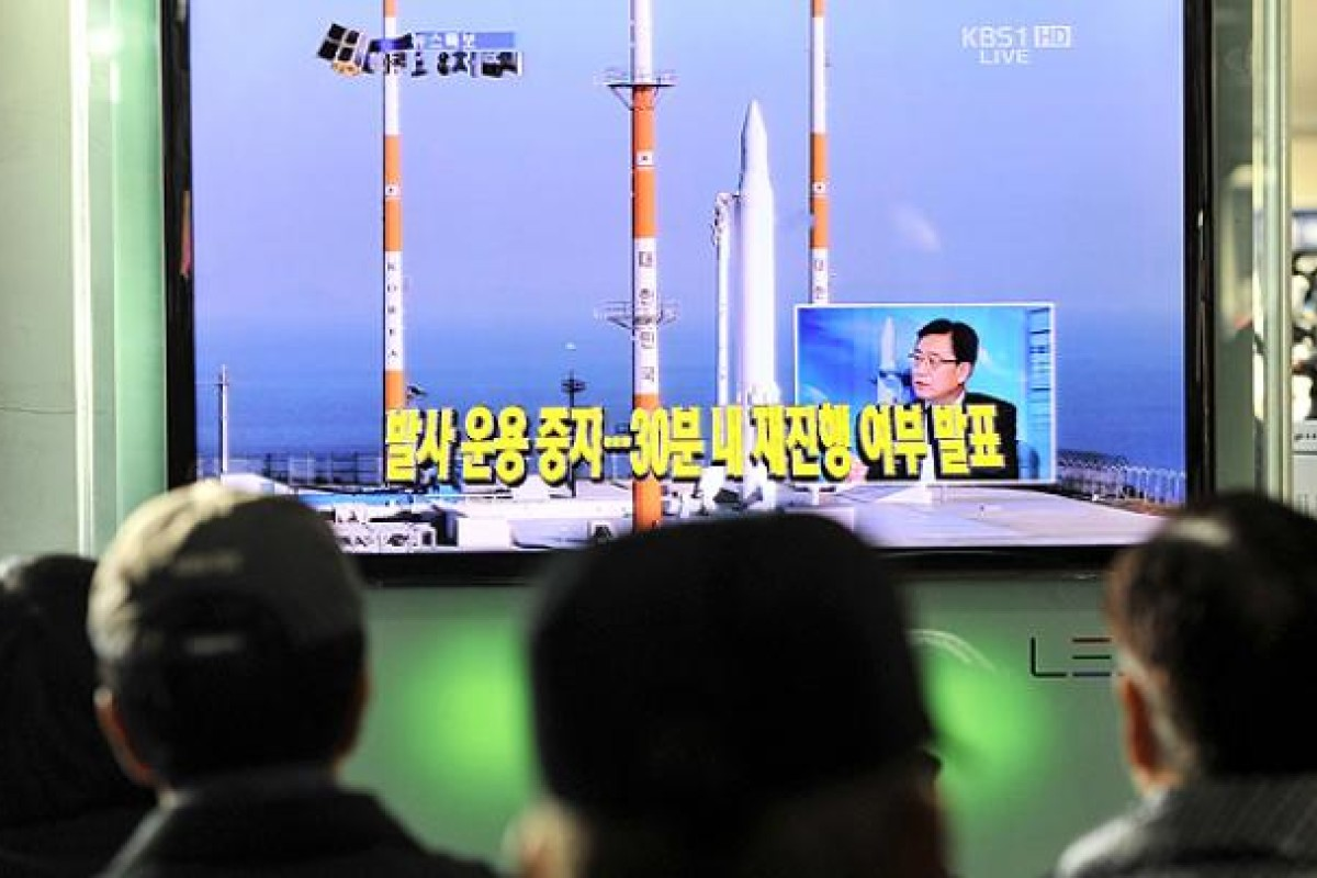 8653ba5f7f8f Commuters watch a live broadcast of South Korea s third attempt at a rocket  launch at a