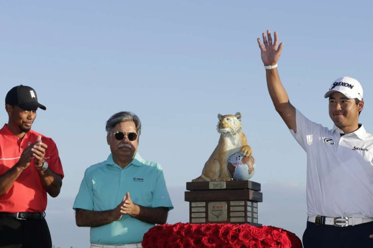 64fdf4f91438 Hideki Matsuyama waves at the trophy presentation with Tiger Woods and  Pawan Munjal