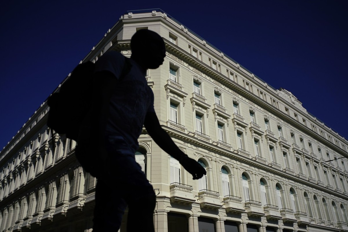 efb0ca2a4d2 A man walks in front of the Manzana de Gomez Kempinski five-star hotel in