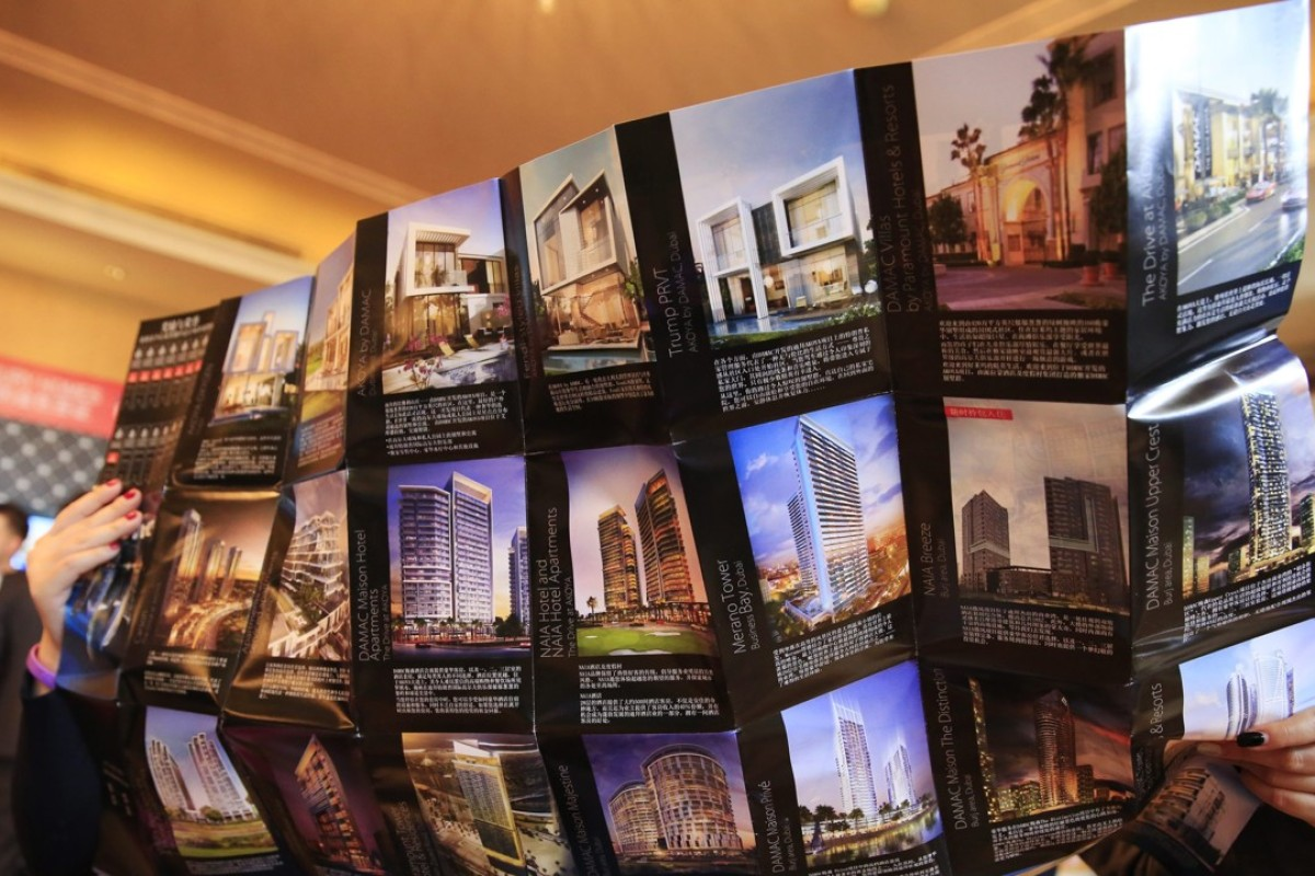a0ba7ddc20ca2 Visitors look at a brochure of luxury properties at a marketing event in  Beijing, in