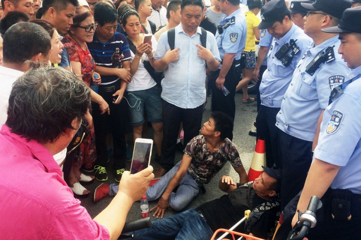 People trying to join a protest against a fraudulent investment scheme in Beijing on Monday lie on the ground after being blocked by police. Photo: Kyodo