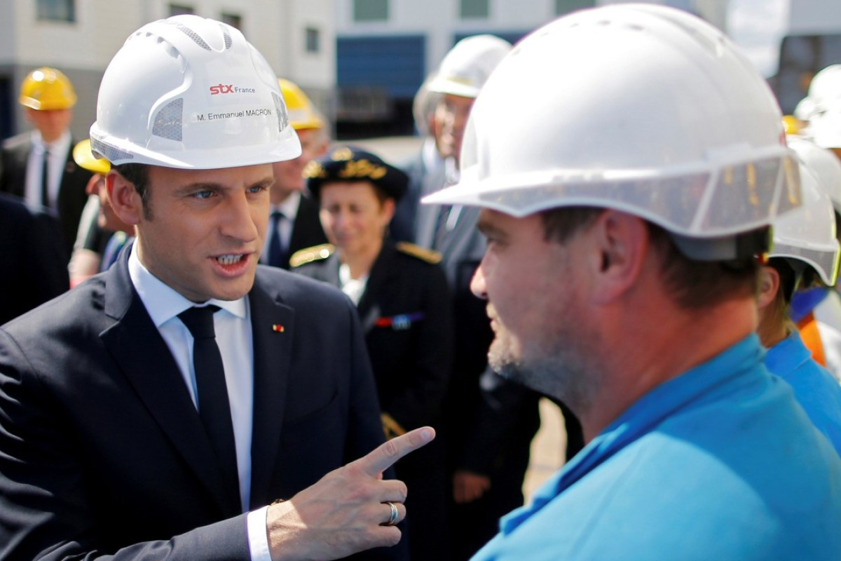 e76782a3 French President Emmanuel Macron (L) speaks to an employee during a visit  to the