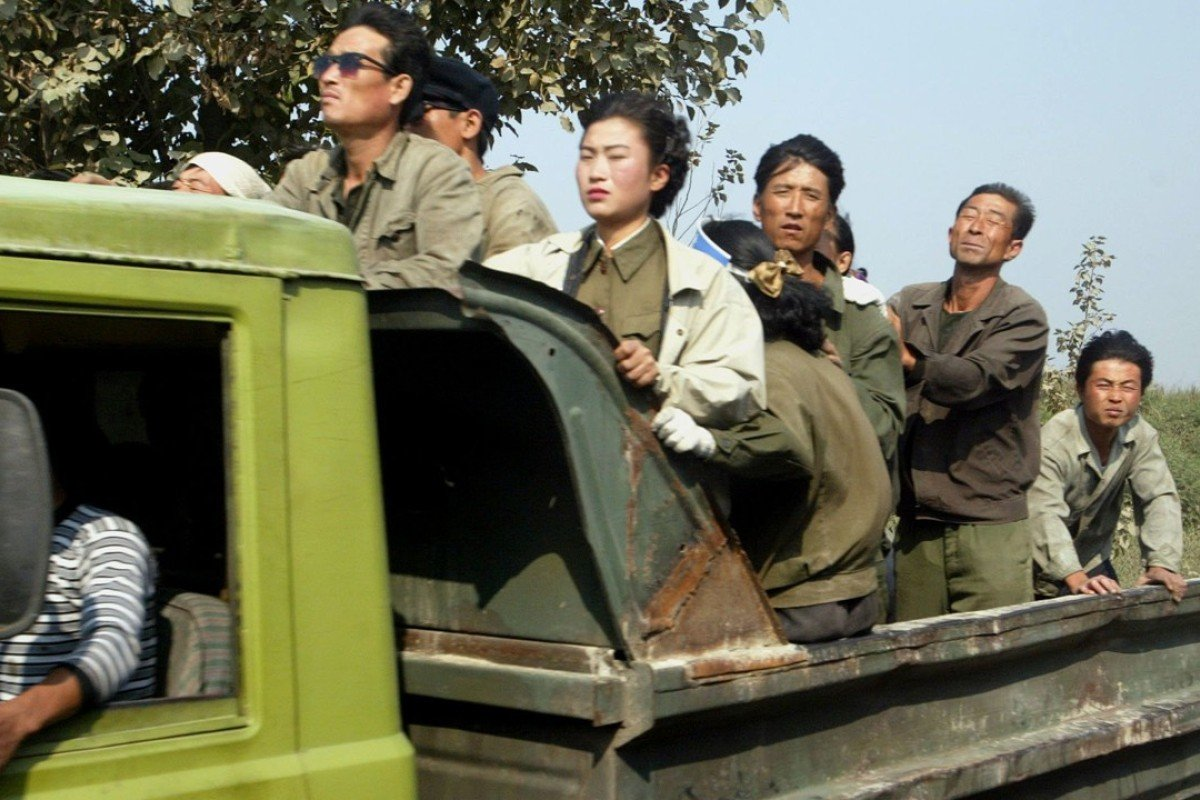 f101b254ef0 A group of North Korean farm labourers and soldiers in a truck driving  along a country