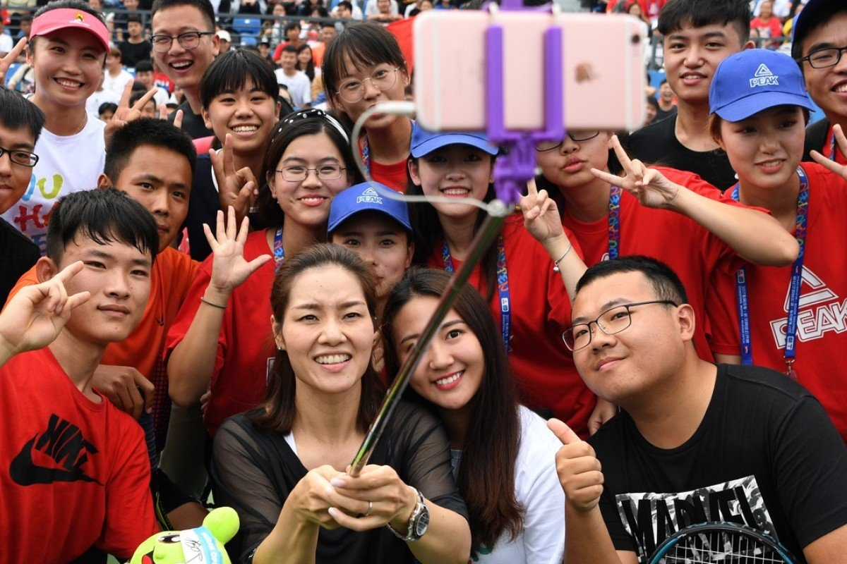 China's two-time grand slam champion, Li Na, takes selfies with young tennis players during the 2017 WTA Wuhan Open. Photo: Xinhua