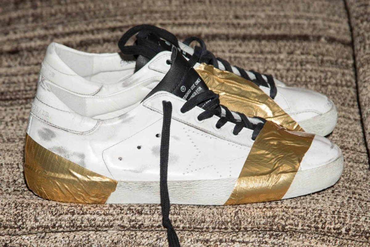 7a03d4859b7 A pair of vintage-looking sneakers featuring golden tape from Golden Goose  Deluxe s autumn-