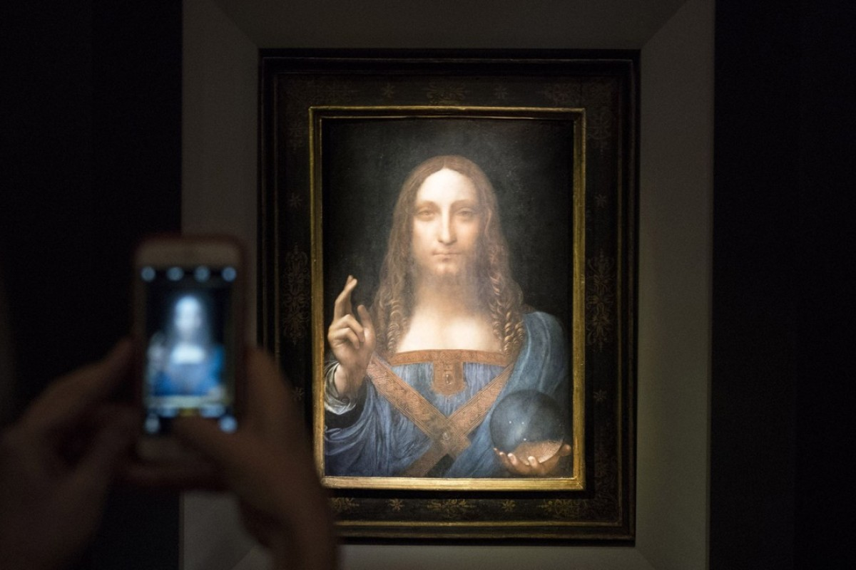 46a1b5aeb1 A visitor takes a photo of the painting Salvator Mundi by Leonardo da Vinci  at Christie s