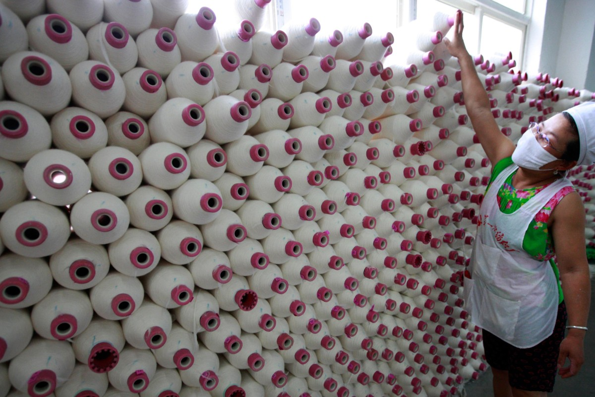 A factory worker with spools of cotton in Huaibei, in eastern China's Anhui province. Photo: AFP