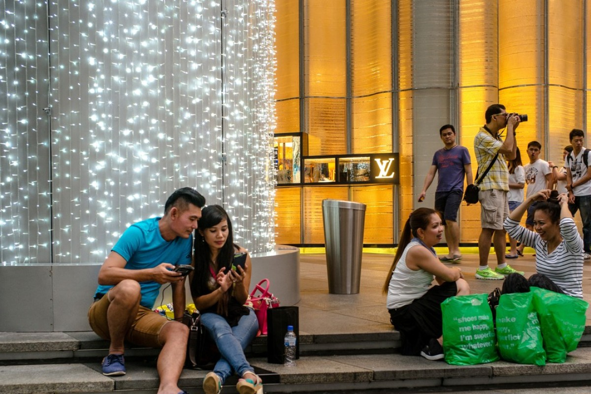 d20895ab2 Shoppers sit on a set of steps outside a LVMH Moet Hennessy Louis Vuitton  SA store