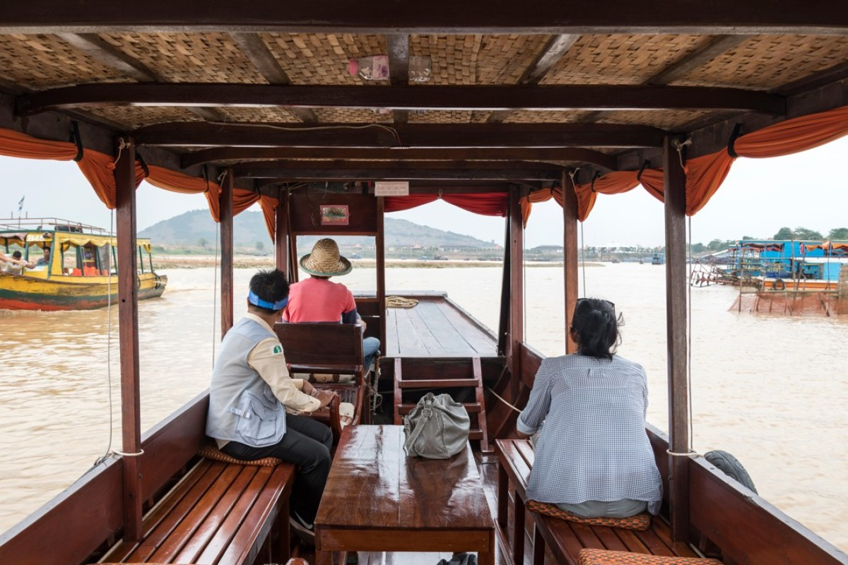 A tourist enjoys a private cruise tour with her guide on Tonle Sap Lake, Siem