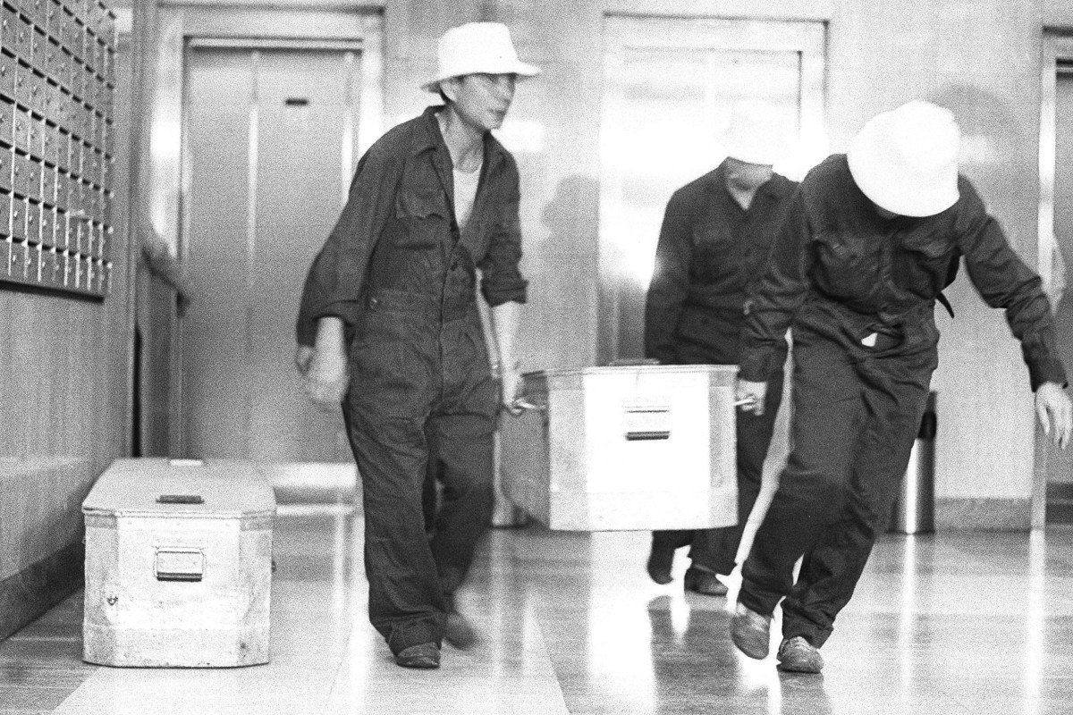 Mortuary staff putting one of the corpses into a temporary coffin. Two bodies were uncovered in a flower bed at Elizabeth House in 1984. Photo: Chan Kiu