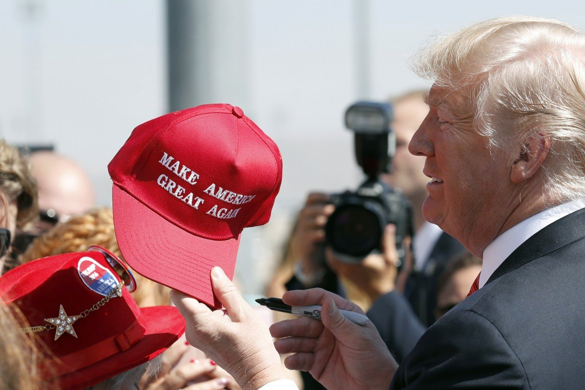 39144a565 President Donald Trump hands a signed 'Make America Great Again' hat to a  supporter