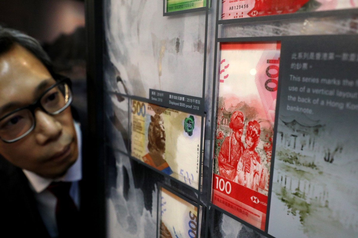 Tommy Tam, art director at HSBC's Global Publishing Services, examines banknotes on display at a special exhibition of historical and current banknotes. Photo: Felix Wong