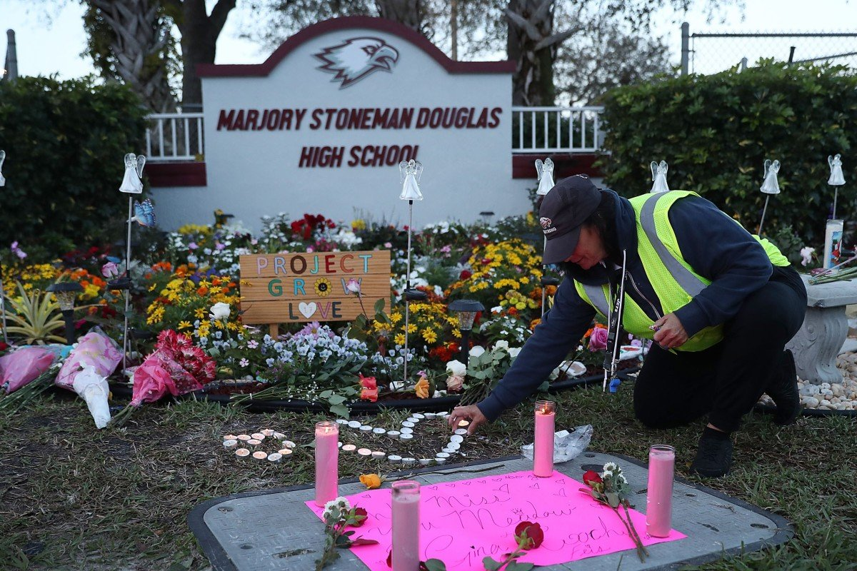 Wendy Behrend, a school crossing guard who was on duty one year ago when a shooter opened fire in Marjory Stoneman Douglas High School, pays her respects at a memorial to those killed on February 14, 2018, in Parkland, Florida. Photo: AFP