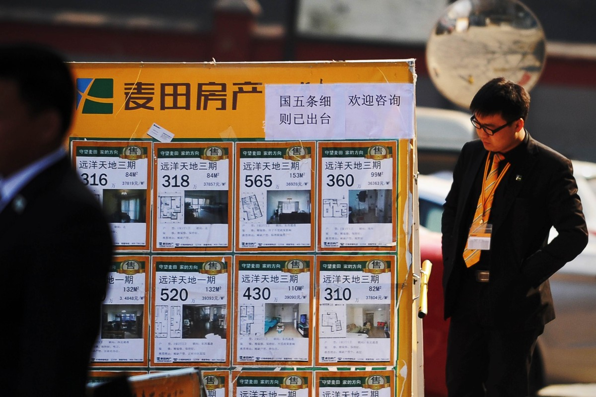 A real property agent checks a property advertising board in Beijing. According to a report by the Chinese government, property brokerages are among the country's least scrupulous group of firms. Photo: Agence France-Presse