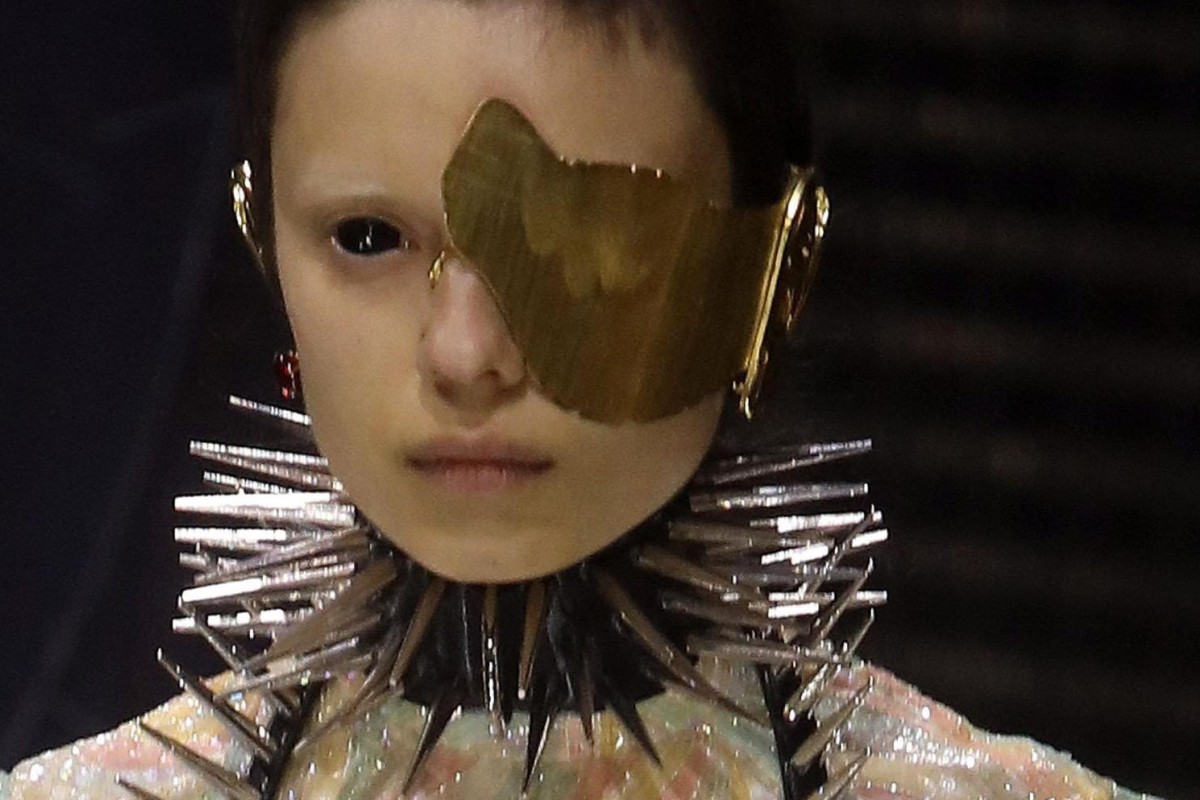 0146a1b408d8 A catwalk model wears a mask while presenting creations from Gucci s  autumn winter 2019
