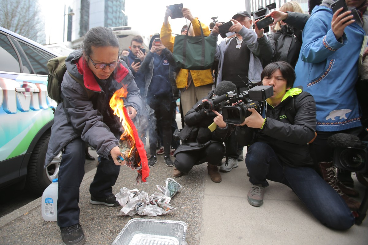 Yang Kuang burns a Chinese flag outside the British Columbia Supreme Court complex in Vancouver, where Huawei Technologies CFO Meng Wanzhou was appearing before a judge. Photo: AFP