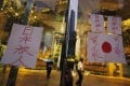 Security guards look on where a drawing of a Japanese national flag and protest slogans are displayed by protesters from an office building where the Japanese Consulate is located in Hong Kong August 15, 2012. REUTERS Bobby Yip