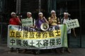 """Anti-Japan protesters show the banner reading """"Release Chinese activists immediately, Sovereignty of Diaoyu Islands cannot be invaded"""" during a rally outside the Japanese Consulate General in Hong Kong Thursday Aug. 16, 2012. China's official Xinhua News Agency said the arrests of the 14 people, who included Hong Kong residents and mainland Chinese, had caused tensions over its territorial dispute with Japan to surge """"to a new high.""""  AP Photo/Kin Cheung"""