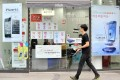 A man walks past signboards of Samsung Electronics' Galaxy S3 (right) and Apple's iPhone 4s at a shop in Seoul, where the court ruling was handed down yesterday. Photo: AFP