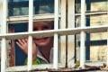 Jailed former Ukrainian Prime Minister Yulia Tymoshenko waves to supporters from a prison window in Kiev, Ukraine. Photo: AP