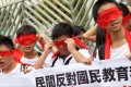 Students cover their eyes with red ribbons during a march against national education in Hong Kong on August 26, 2012. SCMP