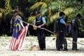 Thai police officers take down a Malaysian flag hoisted in protest by militants in the southern province of Narathiwat on Friday. Photo: AFP