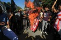 Palestinian men burn the US flag during a demonstration against a film deemed offensive to Islam, on September 12, 2012  in front of the United Nations headquarters in Gaza City.  Photo: AFP