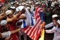 Bangladeshi Muslims burn flags of the US and Israel during a protest in Dhaka on Friday. Photo: AP