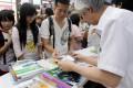 Students and parents check the cost of buying secondary school textbooks at a shop in Mong Kok. Secondary school book prices have gone up on average by 2.5 per cent.Photo: Dickson Lee