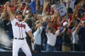 Standing on third base, Atlanta Braves' Chipper Jones reacts along with Braves fans as Freddie Freeman hits a two-run home run to beat the Marlins 4-3 and clinch a wild-card berth for the Braves, at Turner Field in Atlanta on Tuesday. Photo: Associated Press