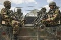 Kenyan soldiers serving with the African Union Mission in Somalia (Amisom) sit on the back of a military vehicle in southern Somalia on Sunday. Photo: AP
