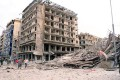 Syrian security officers run from buildings where triple bombs exploded in an Aleppo square on Wednesday. Photo: AP