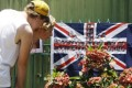 Tourists look at pictures of Bali bombing victims attached to an Australian flag near the 2002 Bali Bombing memorial Monument in Kuta, Bali. Photo: EPA