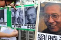 A protester tapes images of Mo Yan (left) and Liu Xiaobo to a gate during a demonstration in front of the Chinese liaison offices in Hong Kong on Saturday. Photo: AFP