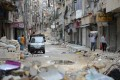 Civilians carry belongings down a street strewn with debris in Aleppo. Photo: AFP