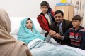 Malala Yousufzai in her hospital bed, with her father Ziauddin (second right) accompanied by her two younger brothers Atal (right) and Khushal (centre). Photo: AP