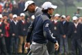 Tiger Woods and Rory McIlroy cross paths on the 10th green during their exhibition showdown at the Lake Jinsha Golf Club in Zhengzhou yesterday. Photo: AFP