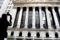 A tourist takes photos of the New York Stock Exchange in Manhattan. Photo: Xinhua