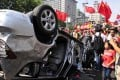 Demonstrators hold Chinese flags and banners beside an overturned Japanese brand car during a protest in Xi'an, Shaanxi province on September 15. Photo: Reuters