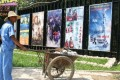 A worker pauses by cinema posters advertising Chinese and English language films in Beijing. Photo: Bloomberg