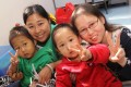 Wu Huiyong (top, in green) with her twins Fu Sze-yu and Fu Sze-ki and volunteer Ruth Yun Mo-tak, a cancer survivor. Photo: K.Y. Cheng