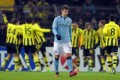 Manchester City's Matija Nastasic walks away dejected as Borussia Dortmund players celebrate victory in their Champions League group D match in Dortmund. Photo: EPA