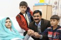 Ziauddin Yousafzai is seen with Malala and her two younger brothers Khushal Khan and Atal Khan (right) at The Queen Elizabeth Hospital in October. Photo: Reuters