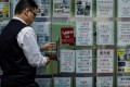 A Hong Kong estate agent shuts up shop, during what has been a difficult period. Photo: AFP
